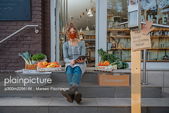 Young female owner with digital tablet sitting on staircase against organic store during COVID-19 - p300m2256186 by Mareen Fischinger