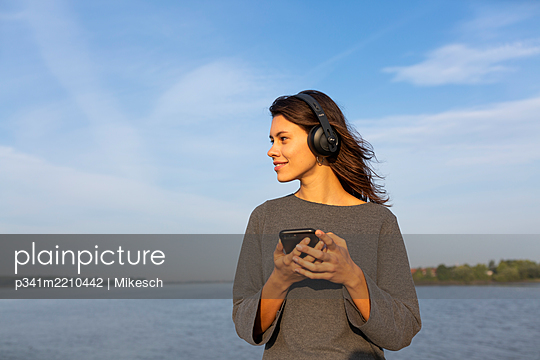 Young woman with headphones and smartphone at the Elbe river - p341m2210442 by Mikesch