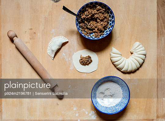 High angle close up of gyoza ingredients and rolling pin on wooden board in a Ramen and Gyoza restaurant in Italy. - p924m2196781 by Senserini Lucrezia