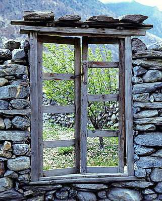 Derelict wooden window frame in dry stone wall with view of apple orchard beyond, Mustang District, Nepal - p3490390 by Elsa Young