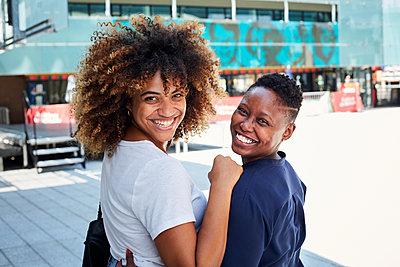 Portrait of smiling Black women hugging in city - p555m1231808 by Granger Wootz