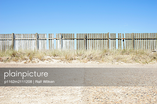 Wooden fence and washed concrete on the coast - p1162m2111208 by Ralf Wilken