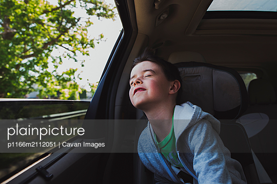 Cute boy with eyes closed traveling in car - p1166m2112051 by Cavan Images