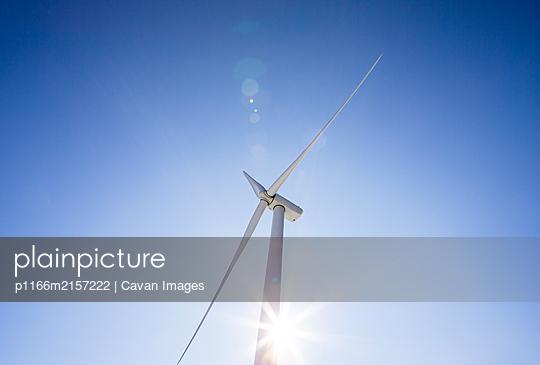 Wind turbine low angle against blue sky - p1166m2157222 by Cavan Images