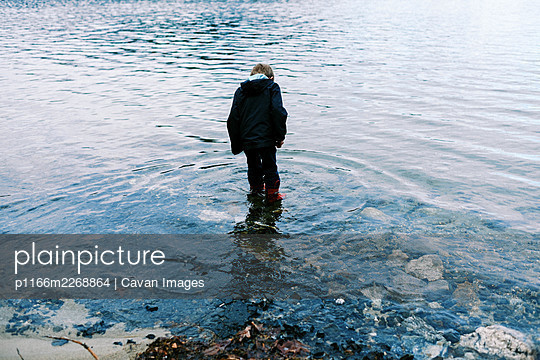 Little boy in red rubber boots walking through blue pristine water - p1166m2268864 by Cavan Images
