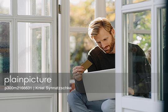 Man using laptop and credit card in sunroom at home - p300m2166631 by Kniel Synnatzschke
