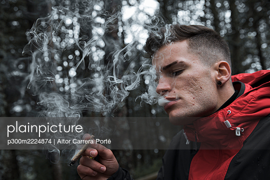 Young man smoking cigarette while standing in forest during autumn - p300m2224874 by Aitor Carrera Porté