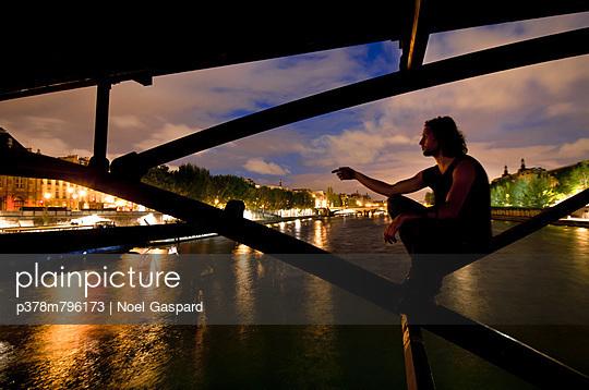 Man sitting under bridge - p378m796173 by Noel Gaspard