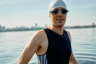 Young athlete in swimming goggles and cap looking at camera - p1630m2203540 by Sergey Mironov