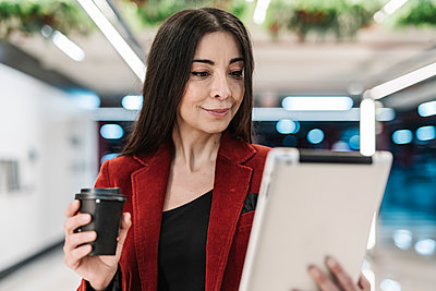 Smiling mature businesswoman with coffee cup looking at digital tablet in subway station - p300m2265909 by COROIMAGE