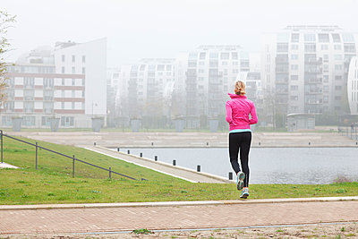 Woman exercising while jogging at park - p300m2293461 by Frank van Delft