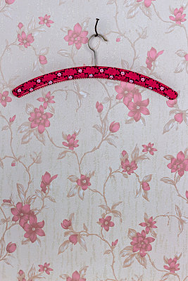 Clothes hanger fixed with a bent nail hanging on wallpaper with pink floral design - p300m949780f by EJW