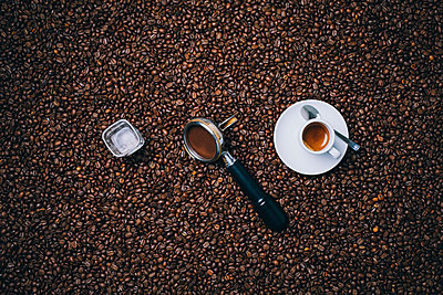 Directly above shot of espresso cup with filter and glass on roasted coffee beans - p301m1498787 by Norman Posselt