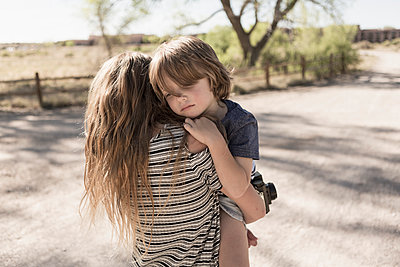 Caucasian girl carrying brother on dirt path - p555m1491008 by Marc Romanelli