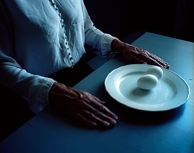 Woman sits at plate with two eggs - p945m1163025 by aurelia frey