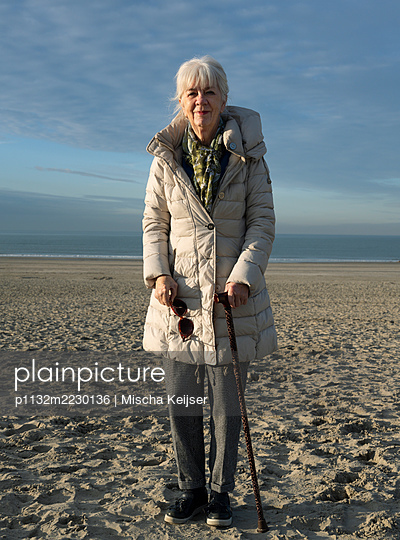 Woman with walking stick by the sea - p1132m2230136 by Mischa Keijser