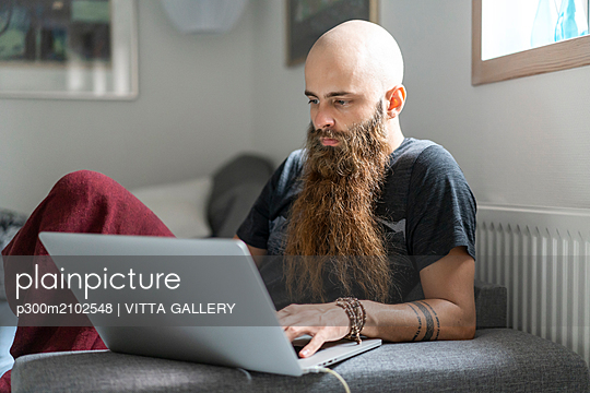 Portrait of hipster using laptop at home - p300m2102548 by VITTA GALLERY