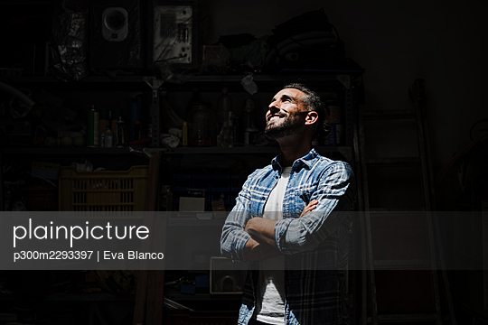 Smiling man with arms crossed standing in front of black background - p300m2293397 by Eva Blanco