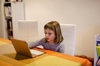 Blonde girl doing her homework on the tablet. Quarantine Covid-19 - p1166m2179583 by Cavan Images