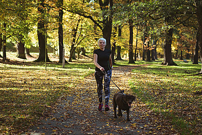 Senior woman walking in the park with her pet dog on a sunny day - p1315m1565682 by Wavebreak