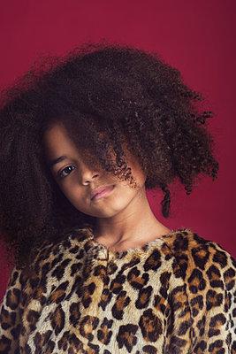 Studio portrait of a girl in animal print fur coat - p1323m2065835 von Sarah Toure