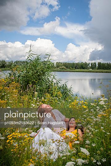 Zwei Freundinnen entspannen sich am Seeufer - p1093m2193622 von Sven Hagolani