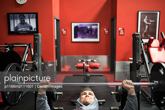 Fit millennial training pectoral muscle with bench press in gym - p1166m2111601 by Cavan Images