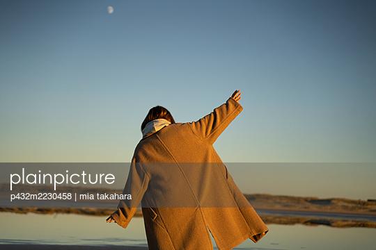Frau im Mantel steht am Strand von St. Peter Ording - p432m2230458 von mia takahara