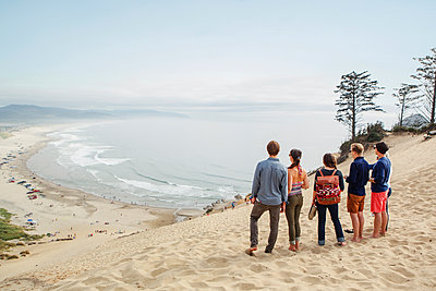 Friends standing together on sand at beach against sky - p1166m1533993 by Cavan Images