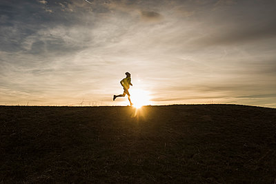 Man running in rural landscape at sunset - p300m1355856 by Uwe Umstätter