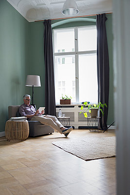 Mature man using tablet at home - p300m2030168 by Rainer Berg