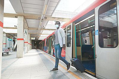 Male entrepreneur business travel disembarking metro train at station during pandemic - p300m2241551 von Pete Muller