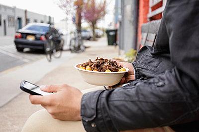Hispanic man eating bowl of food on sidewalk using cell phone - p555m1305247 by Roberto Westbrook