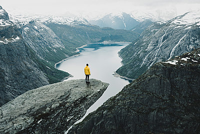 Caucasian man on cliff admiring scenic view of mountain river - p555m1522712 by Alexey Karamanov
