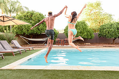 Couple holding hands jumping into swimming pool - p555m1522734 by Kolostock