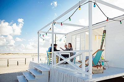 Friends enjoying holiday at beach hosue  - p788m1133322 by Lisa Krechting