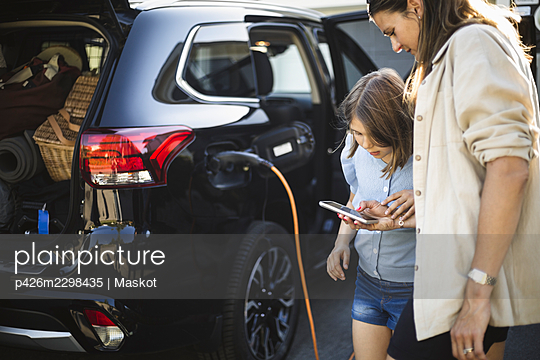 Portrait of mother, father and two daughters standing by car at electric vehicle charging station - p426m2298435 by Maskot