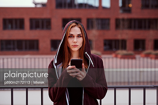 Young woman with smartphone and hooded jacket - p890m2172113 by Mielek