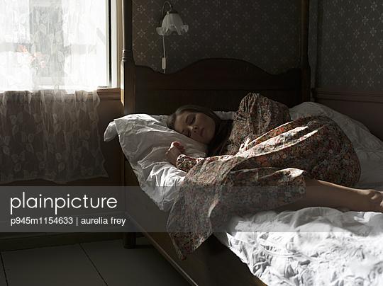 Junge Frau liegt im Bett - p945m1154633 von aurelia frey