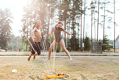 Cheerful kids playing with water - p312m2051485 by Lina Arvidsson