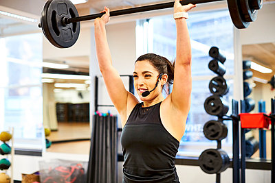 Fitness instructor lifting weights - p343m2046930 by Josh Campbell