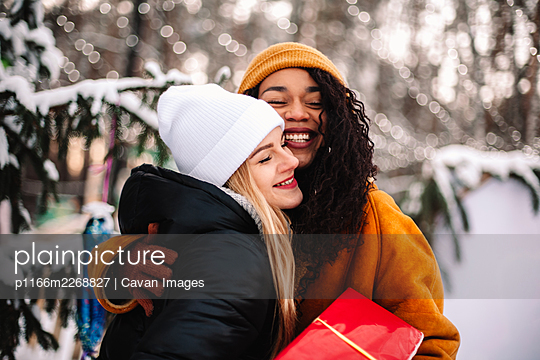 Happy girlfriends embracing holding Christmas gift by Christmas tree - p1166m2268827 by Cavan Images