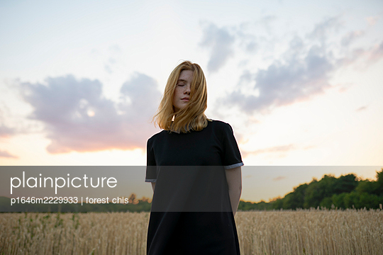 Young woman in a cornfield at dusk - p1646m2229933 by Slava Chistyakov