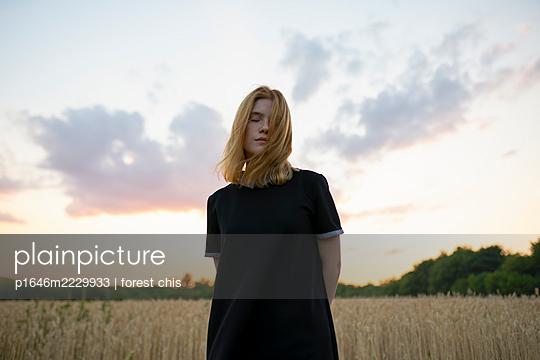 Junge Frau in einem Kornfeld am Abend - p1646m2229933 von Slava Chistyakov