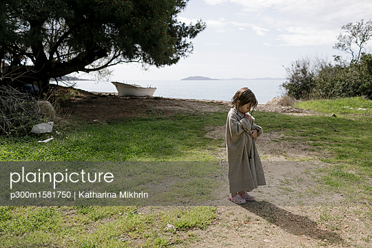 Little girl wrapped in oversized cardigan standing on a meadow - p300m1581750 von Katharina Mikhrin