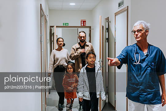 Female doctor with family in surgery - p312m2237216 by Plattform