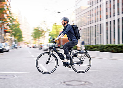 Bicycle courier riding an electric bike - p1124m2053011 by Willing-Holtz