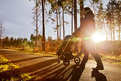 Father and son in buggy on a walk in forest - p300m1189269 by Mareen Fischinger