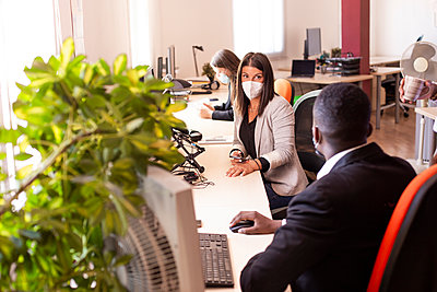 Businesswoman discussing with businessman while sitting at office desk during COVID-19 - p300m2226802 by DREAMSTOCK1982