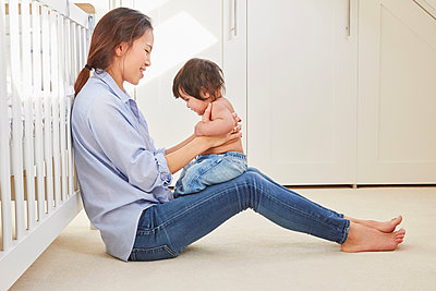 Woman sitting on floor playing with baby daughter on her lap - p429m1447842 by Emma Kim